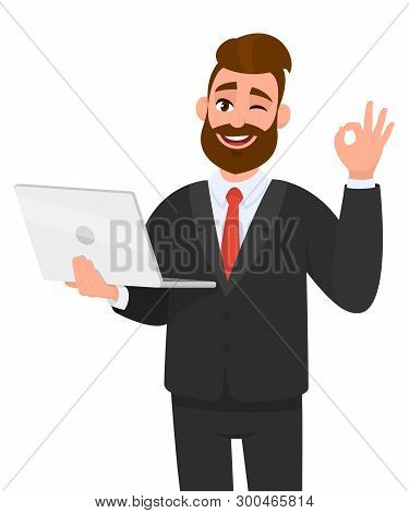 Young Bearded Business Man Is Holding/showing A Latest New Laptop And Gesturing/making Okay Or Ok Si