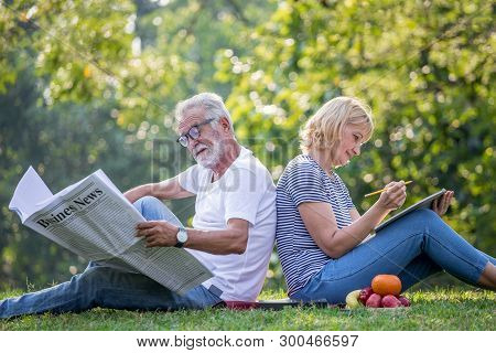 Happy Senior Couple Relaxing Sitting Back To Back In Park Reading Newspaper And Take Write Notes To