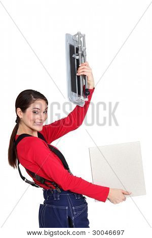 Tradeswoman holding up a tile cutting machine and a tile poster