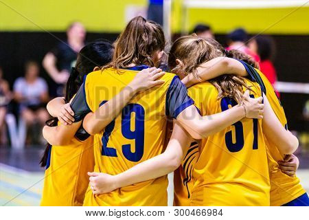 Female Volleyball Players In Yellow Uniform Huddling Together Before Starting The Game