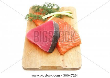 fresh raw salmon and red tuna fish pieces over wooden board isolated on white background . shallow dof
