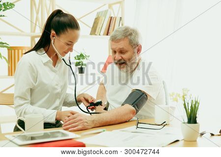 The Visiting Nurse Or Health Visitor Taking Care Of Senior Man. Lifestyle Portrait At Home. Medicine