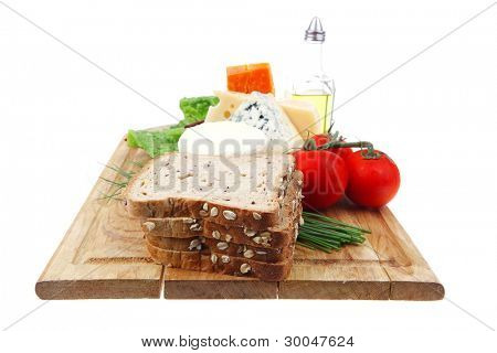 delicatessen cheeses on wooden board with vegetables olive oil and bread isolated over white background