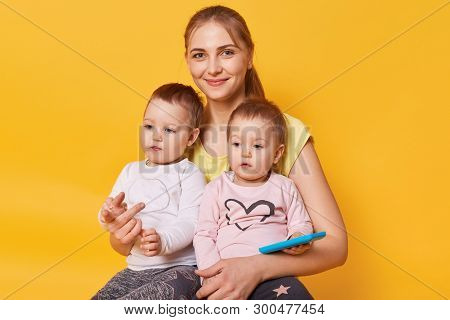 Charming Affectionate Mummy Sitting With Her Cute Little Daughters On Floor In Yellow Studio, Female