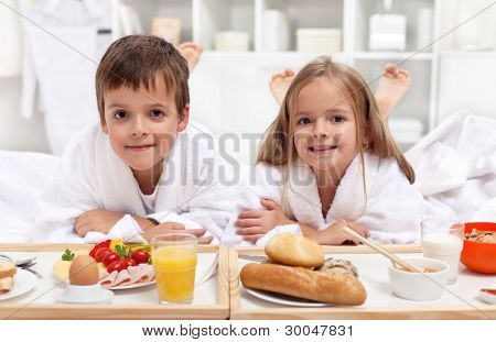 Kids having a healthy and various breakfast in bed