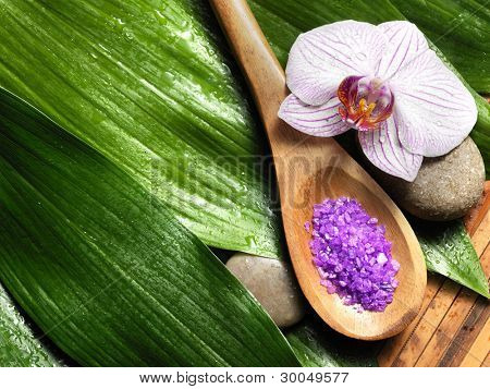 bowl of salt and orchid on leaf