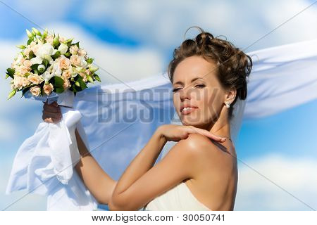 Portrait of a young bride in a white dress with a bouquet of flowers