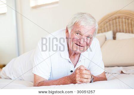 happy elderly man lying on bed