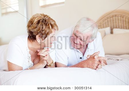 happy senior couple chatting on bed