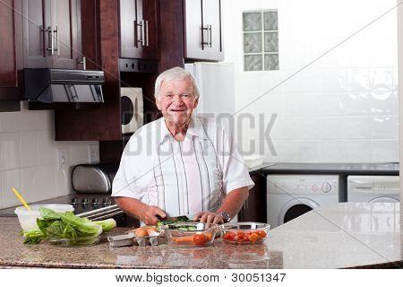 happy senior man preparing food in home kitchen