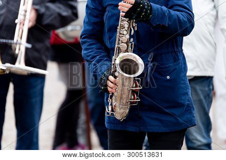 Female Playing Saxohpone Outdoors With A Blue Jacket.