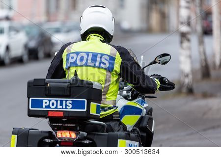 A Swedish Motorcycle Police Officer From Behind.