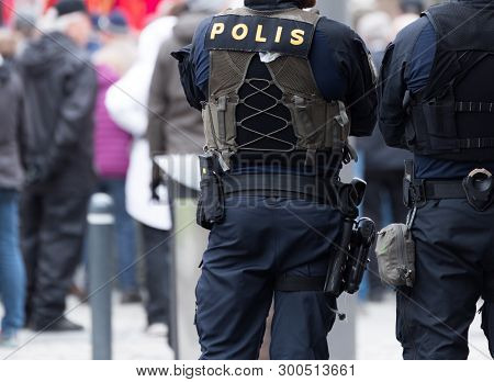 A Swedish Police Officer With Gun From Behind