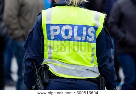 Female Police Officers In Reflective Vest From Behind.