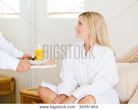 young woman receiving breakfast in bed