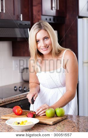 attractive young woman making fruit salad in kitchen