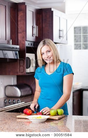 modern young woman cooking in kitchen