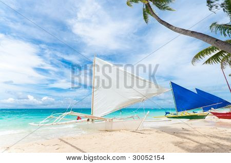 traditional paraw sailing boats on white beach on boracay island Philippines poster