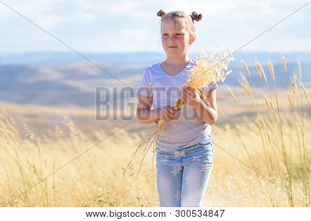 Happy Little Girl Walking In Golden Wheat, Holding Spikes Of Wheat And Ears Of Oats. Nature Beauty,