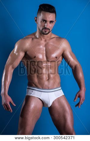 Muscular Handsome Sexy Guy On Blue Background, Naked Torso. Portrait Of Strong Healthy Handsome Athl