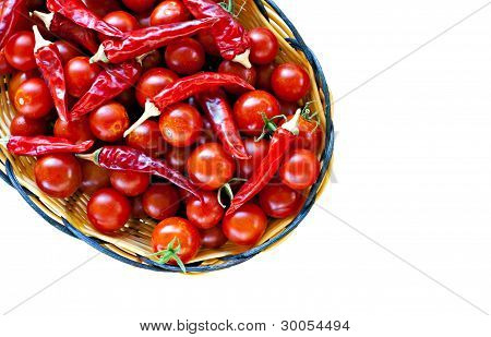 Basket Of Ripe Cherry Tomatoes And Red Chillies