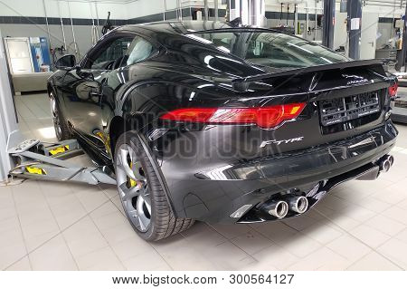 Moscow, Russia - May 1, 2019: Black Jaguar F-type R On A Lift At A Land Rover Service Center. Repair
