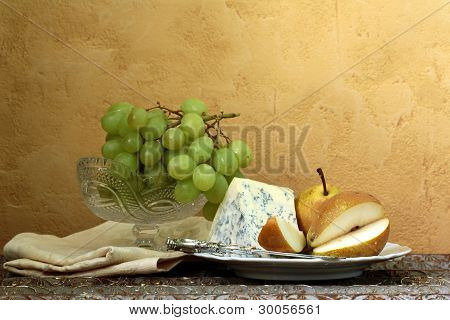 still life  blue cheese, green grapes and pears on the table, vintage