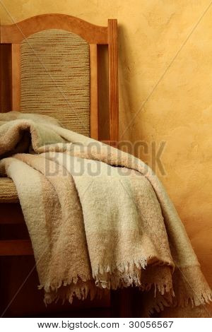 chair with a blanket on a brown background