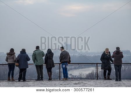 Belgrade, Serbia - February 21, 2015: Tourists Standing On Kalemegdan Fortress Looking At A Foggy Pa
