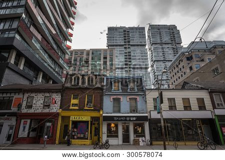 Toronto, Canada - November 13, 2018: Old Individual Houses Surrounded By High Rise Condo Apartment B