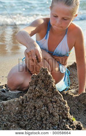 The Girl Builds Sand Castle