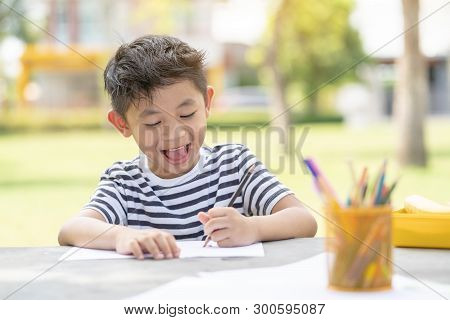 Little Kid Drawing Sketching Cute Adorable. Happy Cheerful Child Drawing With Brush In Album Using A