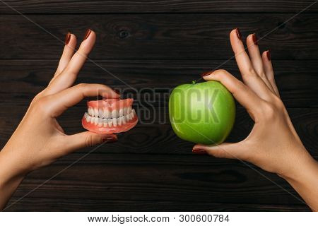 Denture And Apple In The Hands Of A Doctor. False Teeth Denture Against Green Granny Smith Apple. De