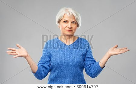 gesture, emotion and old people concept - portrait of senior woman in blue sweater having no idea and shrugging over grey background