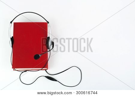 Audiobook On White Background. Headphones Put Over Red Hardback Book, Empty Cover, Copy Space For Ad