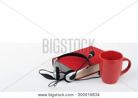 Audiobook On White Background. Headphones Put Over Book, Empty Cover, Red Cup, Copy Space For Ad Tex