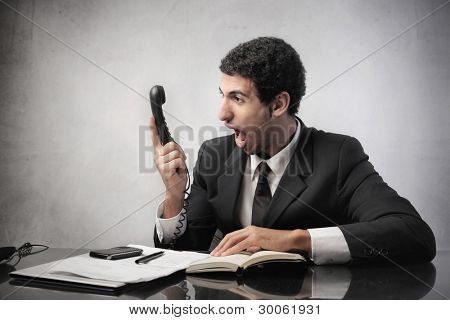 Angry businessman screaming on the telephone