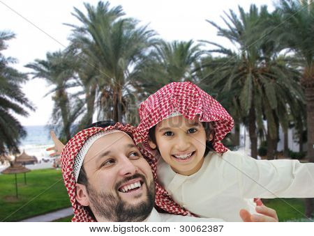 Arabian man and little kid on beach