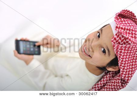 Kid with traditional middle eastern clothes playing with smart phone