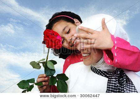 Muslim daughter giving present rose to mother