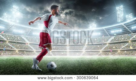 Professional Soccer Player In Action. Ball In Action On The Night Soccer Stadium With Fans And Flags