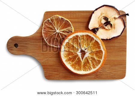 Still Life With Dried Slices Of Orange, Lemon And Apple On The Wooden Cutting Board Against White Ba