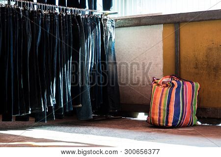 Multi Color On Plastic Sack And The Row Of Denim Pants Hanging On Trempels