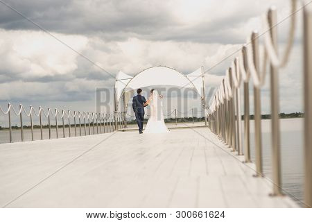The Bride And Groom Walk Along The Painted Light Wooden Pier On A Cloudy Summer Day, Holding Hands.