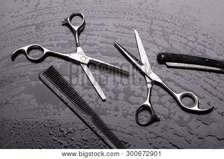 Scissors And A Hairdresser Comb In Drops Of Water On A Dark Background. Barber Scissors. Scissors An