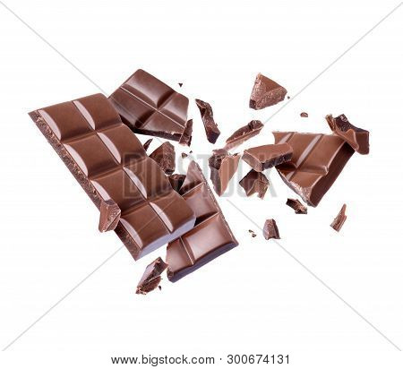 Bar Of Chocolate Is Broken Into Many Pieces In The Air, Isolated On White Background