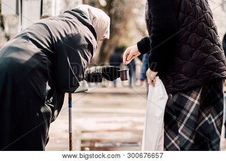 Photo Of Passerby Givining Alms For Old Hungry Homeless Female Beggar On Street
