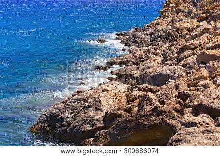 Stone Blocks On The Shore In The Region Lenta On The Island Of Crete. Clear Seawater. Small Waves Be