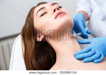 Beautician Doctor With Botulinum Toxin Syringe Making Injection To Platysmal Bands. Neck Rejuvenatio
