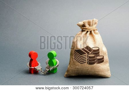 Two People Are Handcuffed To Each Other And Stand Near A Money Bag. Unclosed Obligations Between Two
